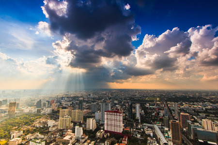 Rays of light shining through dark clouds city Bangkok, Thailand Stock Photo - 24248592