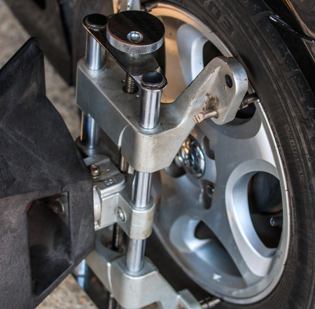 clamped: Car wheel fixed with computerized wheel alignment machine clamp