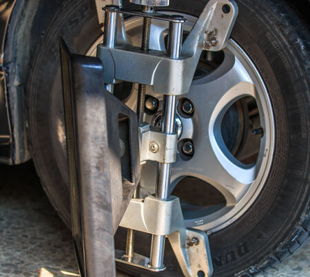 aligning: Car wheel fixed with computerized wheel alignment machine clamp
