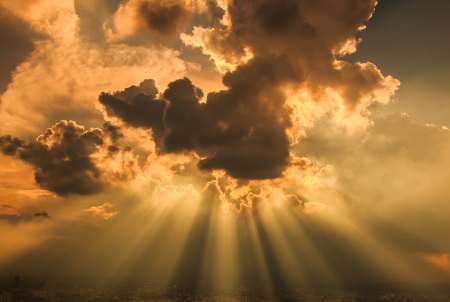 Rays of light shining through dark clouds for background  photo