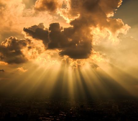 shining through: Raggi di luce attraverso le nuvole scure per lo sfondo Archivio Fotografico
