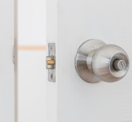 nickle: Detail of a metallic knob on white door , tainless steel round ball door knob  Stock Photo
