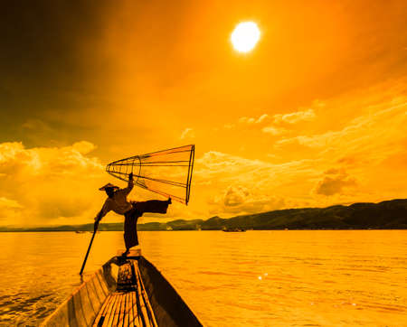 Myanmar Inle lake fisherman on boat catching fish by traditional net in village Inlay Shan state of Myanmar photo