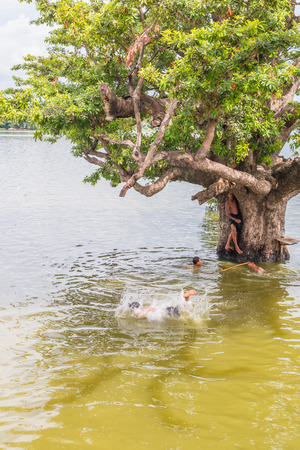 U Bein Bridge, Myanmar-Aug 26th, 2014: Myanmar children were playing by jumping from the tree at the river near U Bein Bridge where is the oldest and longest teak wooden bridge in the world.