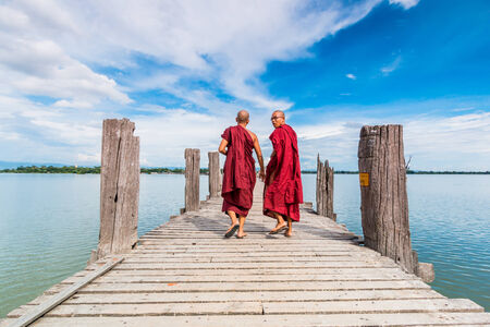 U Bein Bridge, Myanmar-Aug 26th, 2014: Myanmar monks walk on U Bein Bridge where is the oldest and longest teak wooden bridge in the world.