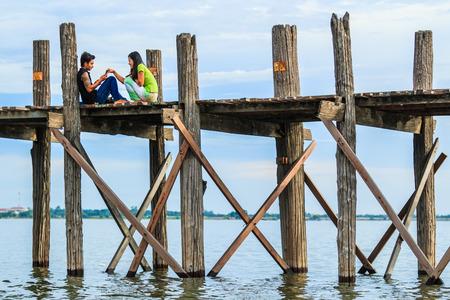 longest: AMARAPURA, MYANMAR - Aug 26th, 2014: An unidentified man rows his boat on Aug 26th, 2014: in Amarapura, Myanmar. Amarapura is famed for the longest teak bridge in the world.