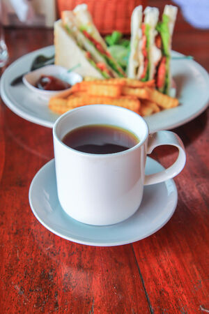 Tea in glass cup and sandwich french fries photo