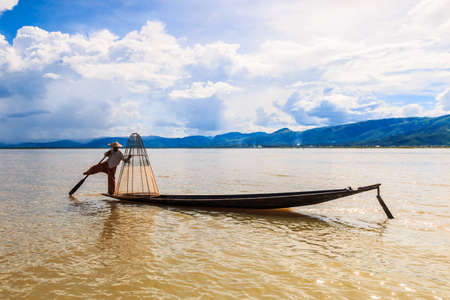 possess: Fisherman catches fish for food on August 24, 2014 on Inle Lake, Myanmar. Intha people possess the leg-rowing style and the unique coop-like fishing equipment Stock Photo