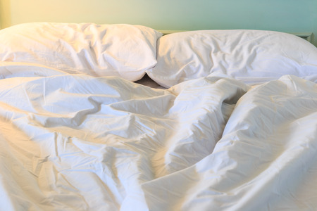 unmade: Messy and unmade bed and Pillows on the bed