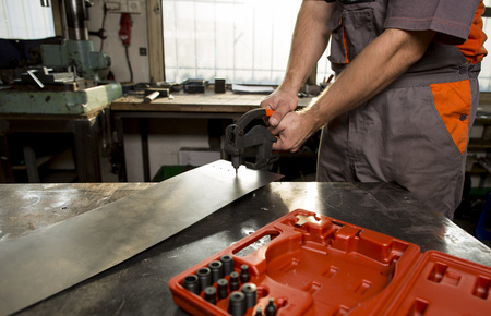 forgeman: Worker holding the manual punch on the workbench in workroom