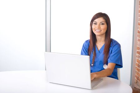 Female nurse at a desk working in a modern office Stock Photo