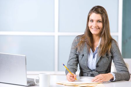 Business woman in modern office with laptop and coffee photo