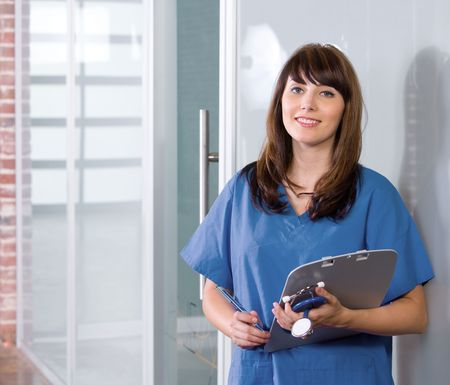 care providers: Female Nurse in a modern office holding a chart
