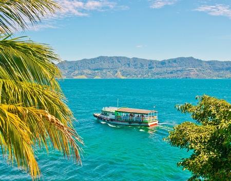 スマトラ インドネシアそれトバ湖でボートは世界で最も大きく、最も深いの火山クレーター湖です。 写真素材