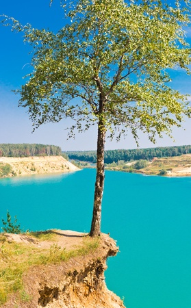 Landscape with lonely tree over blue lake on sky background, Blue Lake, Russia, East Europe Stock Photo