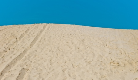 Sand dune with footprints on blue sky background Stock Photo