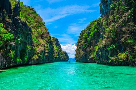 Paisaje tropical con islas rocosas, barco solo y aguas cristalinas, El Nido, Palawan, Filipinas