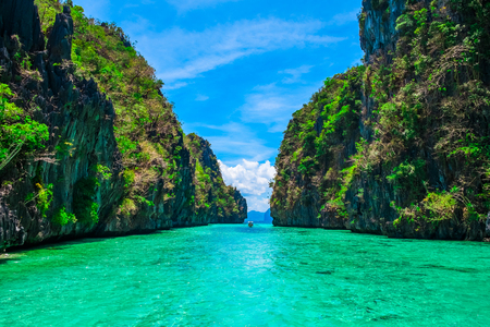 Tropical landscape with rock islands, lonely boat and crystal clear water, El Nido, Palawan, Philippines