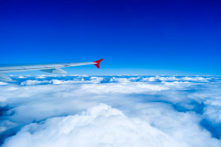 sky: Wing of airplane flying in sky above clouds Stock Photo