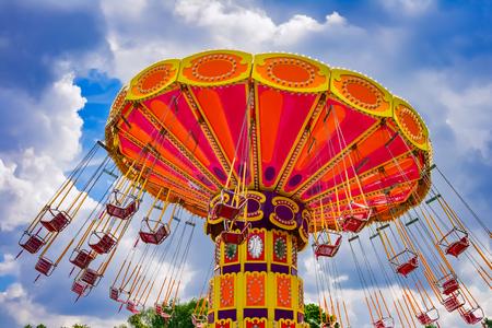 カラフルなスイングに乗る遊園地で 写真素材
