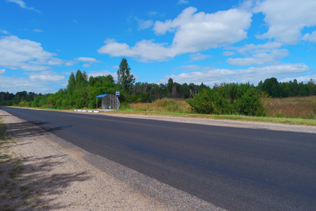 Empty highway with bus stop and green forest