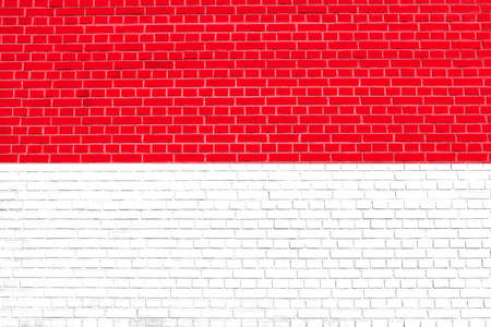 monegasque: Flag of Indonesia, Monaco, Hesse (Germany) on brick wall texture background. Indonesian national flag. Stock Photo
