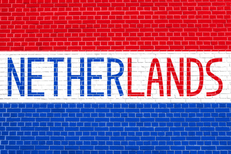 Flag of the Netherlands on brick wall texture background. Word Netherlands.