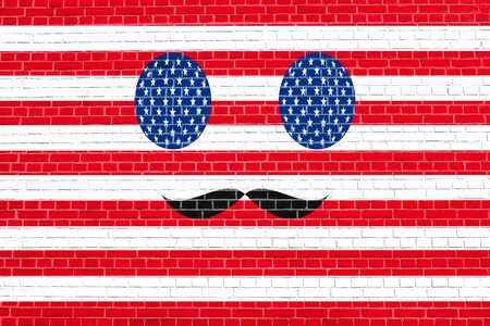 simbols: Funny face made of USA flag simbols with mustaches  on brick wall texture background. Face painted in style of the American flag. Patriotic design in the United States of America flag colors. Stock Photo