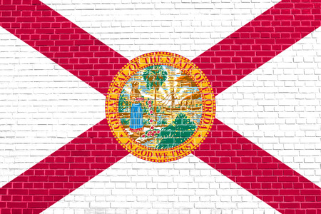 solid state: Floridian official flag, symbol. American patriotic element. USA banner. United States of America background. Flag of the US state of Florida on brick wall texture background