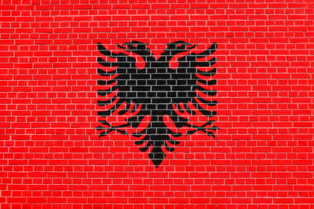 Albanian national official flag. Patriotic symbol, banner, element, background. Accurate dimensions. Correct size, colors. Flag of Albania on brick wall texture background Stock Photo