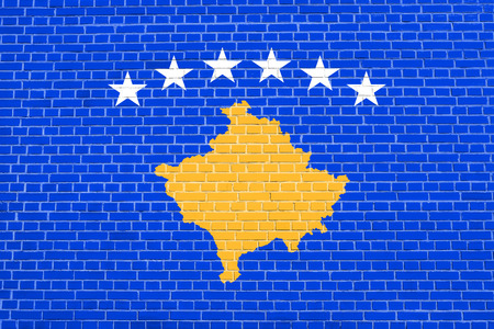 Kosovan national official flag. Patriotic symbol, banner, element, background. Accurate dimensions. Correct size, colors. Flag of Kosovo on brick wall texture background