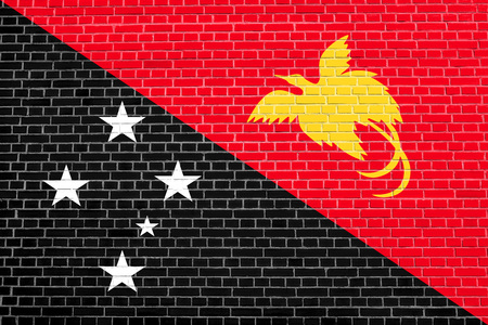 Papua New Guinean national official flag. Papuan patriotic symbol, banner, element, background. Accurate dimensions. Correct size, colors. Flag of Papua New Guinea on brick wall texture background