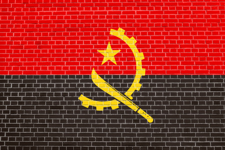 solid state: Angolan national official flag. African patriotic symbol, banner, element, background. Flag of Angola on brick wall texture background