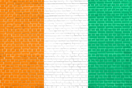 solid state: Cote D Ivoire national official flag. African patriotic symbol, banner, element, background. Flag of Ivory Coast on brick wall texture background
