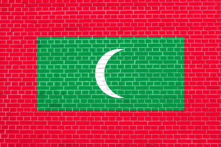 Maldivian national symbol. Patriotic background design. Flag of Maldives on brick wall texture background