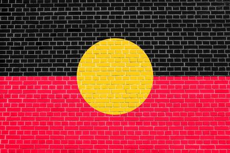 Australian Aboriginal official flag. Commonwealth of Australia patriotic symbol, banner, element, background. Australian Aboriginal flag on brick wall texture background