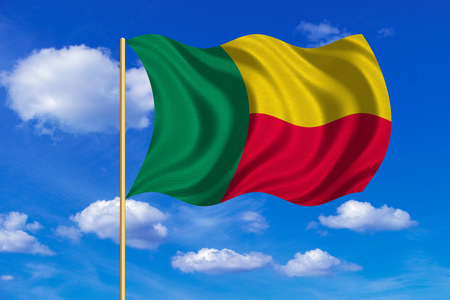 Beninese national official flag. Patriotic symbol, banner, element, background. Correct colors. Flag of Benin on flagpole waving in the wind, blue sky background. Fabric texture