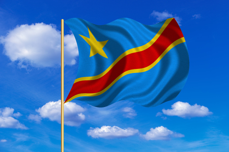 DR Congo national official flag. African patriotic symbol, banner, element. Correct colors. Flag of Democratic Republic of the Congo on flagpole waving in the wind, blue sky background. Fabric texture Stock Photo