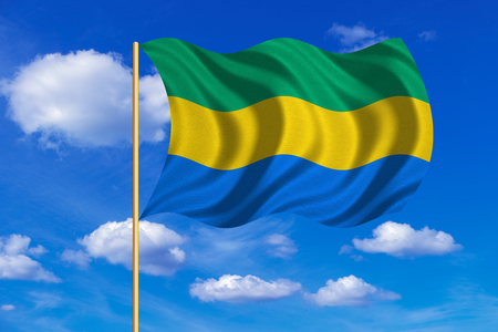 Gabonese national official flag. African patriotic symbol, banner, element, background. Correct colors. Flag of Gabon on flagpole waving in the wind, blue sky background. Fabric texture Stock Photo