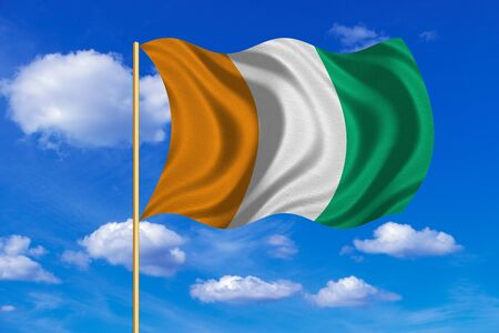 Cote D Ivoire national official flag. African patriotic symbol, banner, element, background. Correct colors. Flag of Ivory Coast on flagpole waving in the wind, blue sky background. Fabric texture