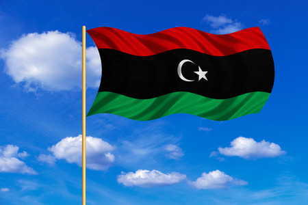 Libyan national official flag. African patriotic symbol, banner, element, background. Correct colors. Flag of Libya on flagpole waving in the wind, blue sky background. Fabric texture