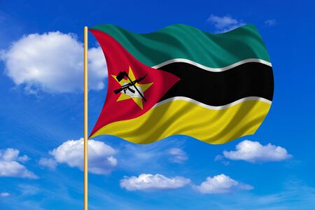 Mozambican national official flag. African patriotic symbol, banner, element, background. Correct colors. Flag of Mozambique on flagpole waving in the wind, blue sky background. Fabric texture Stock Photo