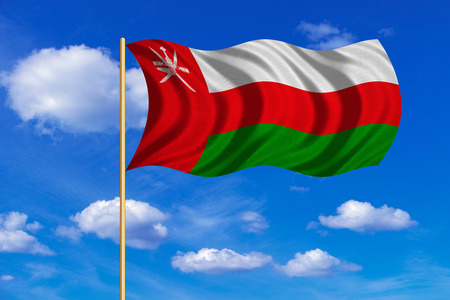 Omani national official flag. Patriotic symbol, banner, element, background. Correct colors. Flag of Oman on flagpole waving in the wind, blue sky background. Fabric texture