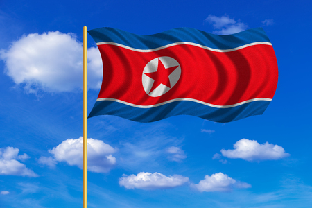 korean national: North Korean national official flag. Patriotic DPRK symbol, banner, element, background. Correct colors. Flag of North Korea on flagpole waving in the wind, blue sky background. Fabric texture