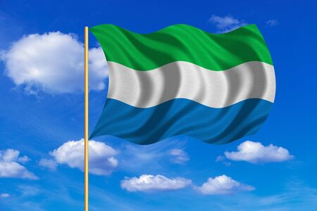 Sierra Leonean national official flag. African patriotic symbol, banner, element, background. Correct colors. Flag of Sierra Leone on flagpole waving in the wind, blue sky background. Fabric texture