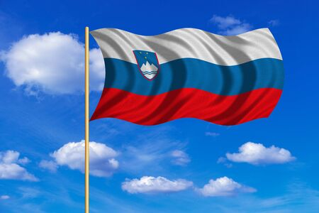 Slovenian national official flag. Patriotic symbol, banner, element, background. Correct colors. Flag of Slovenia on flagpole waving in the wind, blue sky background. Fabric texture