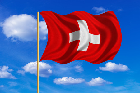 Swiss national official flag. African patriotic symbol, banner, element, background. Correct colors. Flag of Switzerland on flagpole waving in the wind, blue sky background. Fabric texture Stock Photo