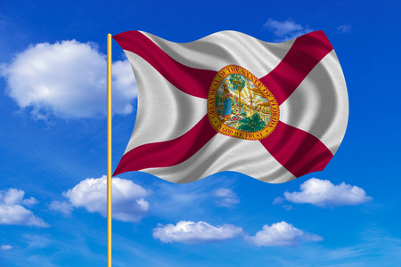 Flag of the US state of Florida. American patriotic element. USA banner. United States of America symbol. Floridian official flag on flagpole waving in the wind, blue sky background. Fabric texture Stock Photo