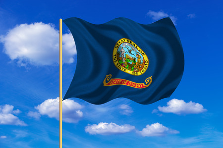 Flag of the US state of Idaho. American patriotic element. USA banner. United States of America symbol. Idahoan official flag on flagpole waving in the wind, blue sky background. Fabric texture