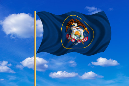 Flag of the US state of Utah. American patriotic element. USA banner. United States of America symbol. Utahn official flag on flagpole waving in the wind, blue sky background. Fabric texture
